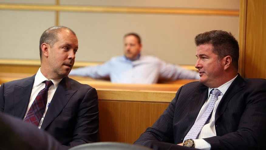 In a Wednesday, May 13, 2015 photo, attorneys Adam Filthaut and Robert Adams, right, talk in court during testimony at the Pinellas County Justice Center in Clearwater, Fla. A Florida judge will soon decide if three well-known Tampa attorneys tricked a rival lawyer into getting a DUI, all to help their defamation case.  (Jay Conner/Tampa Tribune via AP, Pool)