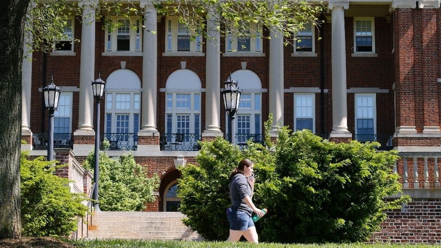 In this photo taken on Wednesday, May 13, 2015, a Sweet Briar College student walks past a building at the school in Sweet Briar, Va..  The school is scheduled to close in August with the final commencement ceremonies Saturday, May 16.   (AP Photo/Steve Helber)