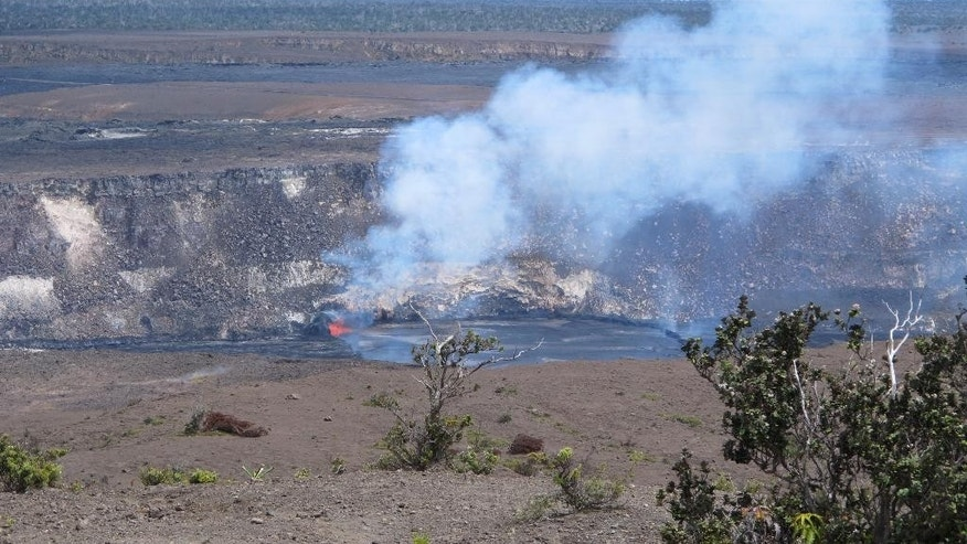 In this Saturday, May 9, 2015 photo, molten rock spews into a lake of lava near the summit of Kilauea volcano on Hawaii's Big Island. The lava lake had reached a record high level on May 8 and then began descending, making scientists wonder where the molten rock will go next. (AP Photo/Cathy Bussewitz)