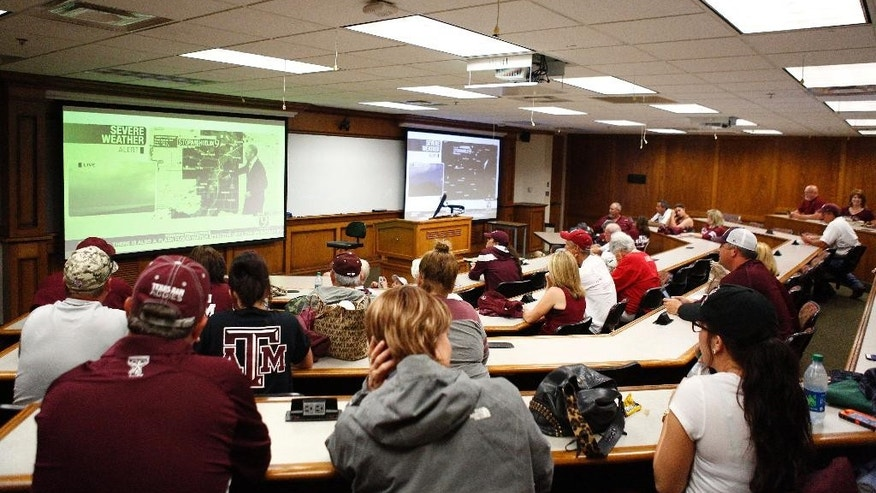 Texas A&M softball fans take refuge in a classroom at the Oklahoma University Law Center after game play was suspended in the third inning of an NCAA college softball tournament regional game due to severe weather, Saturday, May 16, 2015, in Norman, Okla. (AP Photo/Alonzo Adams)