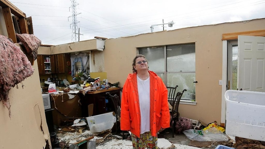 Carol Cole stands in her home in Broken Arrow, Okla., on Sunday, May 17, 2015, after a strong storm hit the area Saturday night and early Sunday morning, destroying the Cole's home. Dangerous weather was centered in southwestern Oklahoma, where tornadoes touched down near Elmer and Tipton, National Weather Service forecaster Daryl Williams said. The most significant damage, according to Oklahoma emergency officials, was to homes, businesses and power lines. (Mike Simons/Tulsa World via AP)