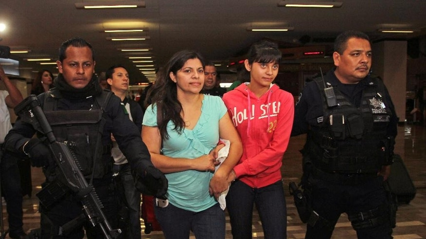 Houston resident Dorotea Garcia and 13-year-old Alondra Diaz are escorted by police as they arrive at the international airport in Guadalajara, Mexico, early Saturday May 16, 2015. Garcia got her long-missing daughter back and headed for home, concluding an eight-year search after Alondra was taken to Mexico in 2007 by her father, Reynaldo Diaz, without her mother's consent, and her whereabouts had not been known until recently. The case gained international attention last month after Mercado erroneously ruled that 14-year-old Alondra Luna was the missing girl and ordered her turned over to Garcia. (AP Photo)