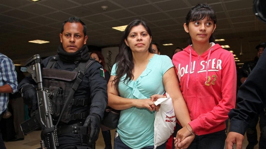 Houston resident Dorotea Garcia, center, and 13-year-old Alondra Diaz are escorted by police as they arrive at the international airport in Guadalajara, Mexico, early Saturday May 16, 2015. Garcia got her long-missing daughter back and headed for home, concluding an eight-year search after Alondra was taken to Mexico in 2007 by her father, Reynaldo Diaz, without her mother's consent, and her whereabouts had not been known until recently. The case gained international attention last month after Mercado erroneously ruled that 14-year-old Alondra Luna was the missing girl and ordered her turned over to Garcia. (AP Photo)