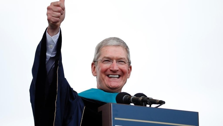 Apple CEO Tim Cook gives a thumbs up while addressing graduates during George Washington University's commencement exercises on the National Mall, Sunday, May 17, 2015 in Washington. The university awarded Cook with an honorary doctorate of public service. (AP Photo/Alex Brandon)
