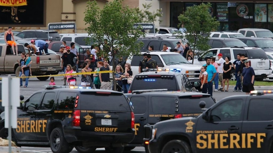 "People at the Central Texas MarketPlace watch a crime scene near the parking lot of a Twin Peaks restaurant Sunday, May 17, 2015, in Waco, Texas. Waco Police Sgt. W. Patrick Swanton told KWTX-TV there were ""multiple victims"" after gunfire erupted between rival biker gangs at the restaurant. (Rod Aydelotte/Waco Tribune-Herald via AP)"