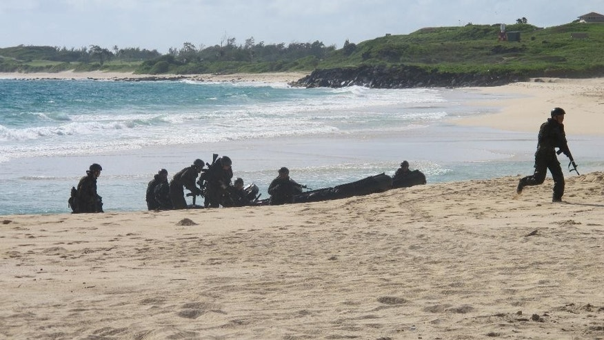 FILE - In this July 29, 2014 file photo, Japanese soldiers on a reconnaissance team come ashore during amphibious landing practice at Kaneohe Bay, Hawaii. Amphibious military capabilities are on the agenda the week of May 18, 2015, as the U.S. Marine Corps and Navy host defense leaders from around the Pacific in Hawaii. (AP Photo/Audrey McAvoy, File)