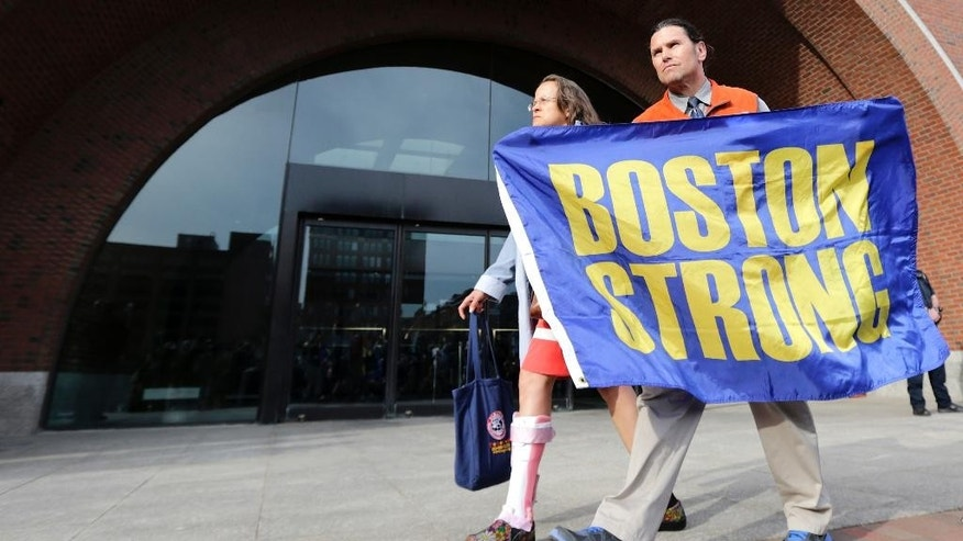 "Boston Marathon bombing volunteer first responder Carlos Arredondo holds a ""Boston Strong"" banner as he leaves the Moakley Federal court with his wife Melida after the verdict in the penalty phase of the trial of Boston Marathon bomber Dzhokhar Tsarnaev, Friday, May 15, 2015. The federal jury ruled that the 21-year-old Tsarnaev should be sentenced to death by lethal injection for his role in the deadly 2013 attack. Carlos is credited with saving the life of bombing survivor Jeff Bauman, who lost both of his legs in the blast. (AP Photo/Charles Krupa)"