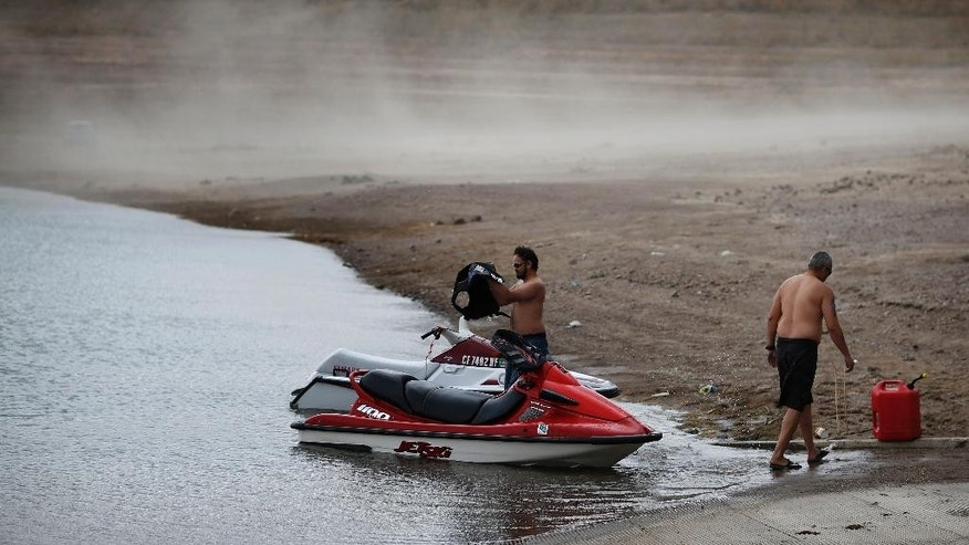 People prepare to launch watercraft as wind kicks up dust on an area that was once underwater at the Boulder Harbor boat ramp in the Lake Mead National Recreation Area, Monday, May 18, 2015, near Boulder City, Nev. Federal water managers are projecting Lake Mead will drop to levels in January 2017 that could force supply cuts to Arizona and Nevada. (AP Photo/John Locher)