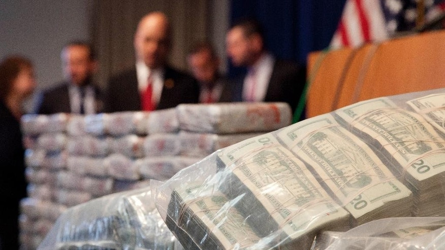 Sacks of money, right, worth $2 million, and 154 pounds of heroin, left, worth at least $50 million, are displayed at a Drug Enforcement Administration news conference, Tuesday, May 19, 2015 in New York. The DEA called the heroin seizure its largest ever in New York state. Officials said on Tuesday that most of the drugs were found in an SUV in the Bronx following a wiretap investigation. (AP Photo/Mark Lennihan)