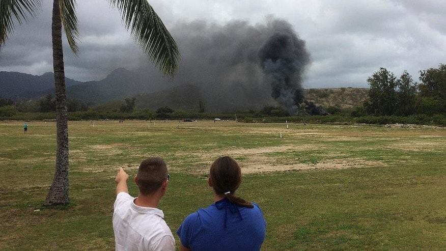 In this May 17, 2015 photo, a man and woman look toward smoke rising from a Marine Corps Osprey aircraft after making a hard landing on Bellows Air Force Station near Waimanalo, Hawaii. The fatal crash of the Marine Corps' new hybridized airplane-and-helicopter aircraft during a training exercise is renewing safety concerns about the machine. (Zane Dulin via AP)