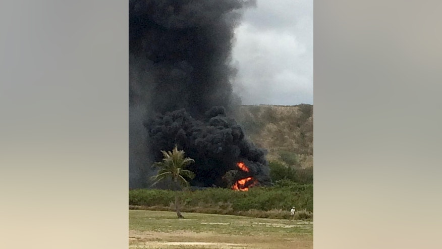 In this May 17, 2015 photo, smoke rises from a Marine Corps Osprey aircraft after making a hard landing near Bellows Air Force Station near Waimanalo, Hawaii. The fatal crash of the Marine Corps' new hybridized airplane-and-helicopter aircraft during a training exercise is renewing safety concerns about the machine. (Zane Dulin via AP)