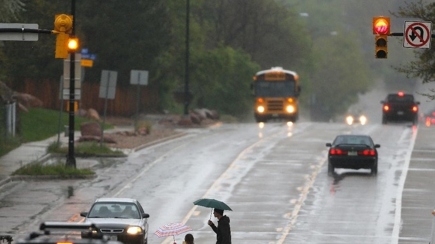A man walks a student to school in the rain, in Boulder, Colo., Tuesday, May 19, 2015. Colorado braced for a spring storm with unseasonably heavy rains and several inches of snow expected in the high country. (AP Photo/Brennan Linsley)