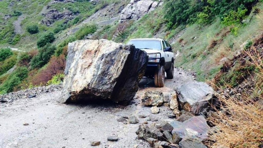 In this Sunday, May 17, 2015 photo provided by the Davis County Sheriff's Office, a large boulder blocks a vehicle on a road in Farmington Canyon, about 20 miles north of Salt Lake City. Spring storms that have been pounding the West hit northern Utah over the weekend, causing minor flooding and a rock slide, with more storms forecasted this week. (Davis County Sheriff's Office via AP)