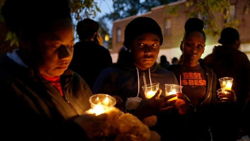 FILE - In this Oct. 9, 2014 file photo, people gather for a candlelight vigil to remember Vonderrit Myers Jr., in St. Louis. An attorney for the family of the black 18-year-old shot and killed last October by an off-duty, white St. Louis police officer said Tuesday, May 19, 2015 he plans to file a wrongful-death lawsuit, after a prosecutor said the officer would not face criminal charges. (AP Photo/Jeff Roberson, File)