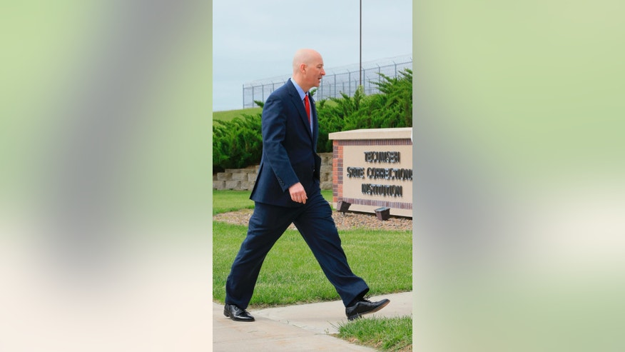 Nebraska Gov. Pete Ricketts walks past a sign for the Tecumseh State Correctional Institution following a tour of the facility in Tecumseh, Neb., Tuesday, May 19, 2015. The tour took place a little more than a week after a riot at the prison left two inmates dead. (AP Photo/Nati Harnik)
