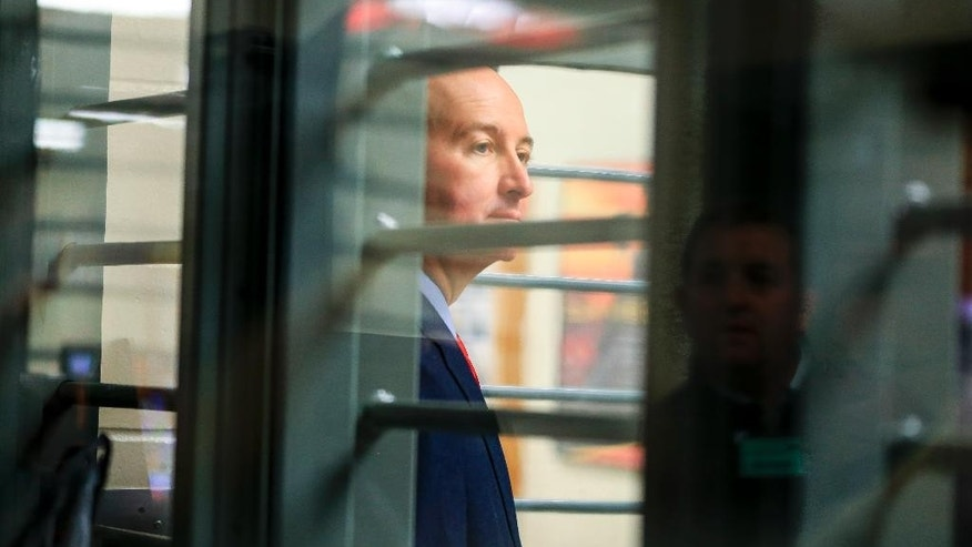 Nebraska Gov. Pete Ricketts is seen through bars during a tour of the Tecumseh State Correctional Institution in Tecumseh, Neb., Tuesday, May 19, 2015. The tour took place a little more than a week after a riot at the prison left two inmates dead. (AP Photo/Nati Harnik)