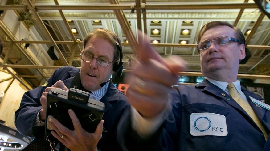 Trader Luke Scanlon, left, and specialist Patrick King work on the floor of the New York Stock Exchange, Tuesday, May 19, 2015. U.S. stocks are edging mostly lower in early trading as the market comes off its latest record high. (AP Photo/Richard Drew)