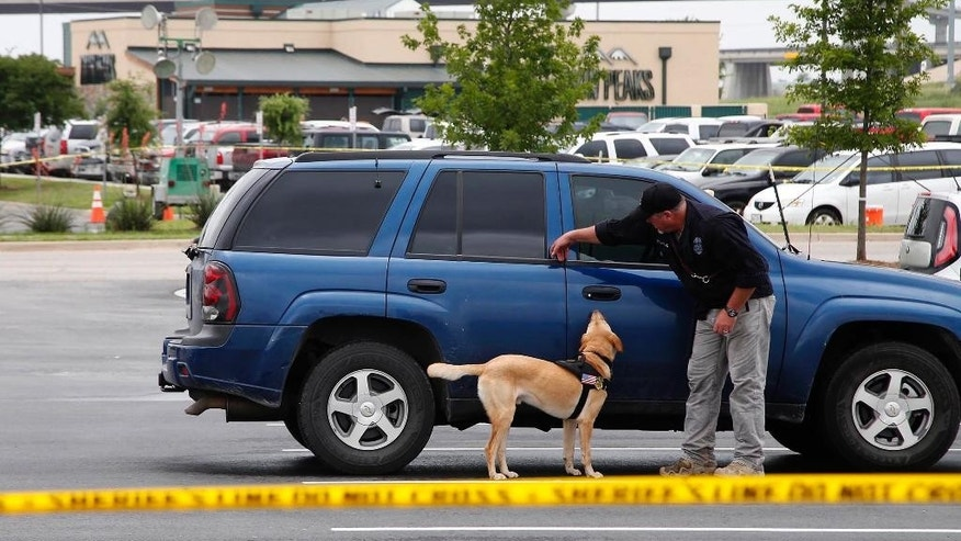Law enforcement officer uses a dog to search parked cars located in part of the Central Texas Marketplace Tuesday, May 19, 2015, in Waco, Texas.  A deadly weekend shootout involving rival motorcycle gangs apparently began with a parking dispute and someone running over a gang member's foot, police said Tuesday. One man was injured when a vehicle struck his foot. That caused a dispute that continued inside the restaurant, where fighting and then shooting began, before spilling back outside, Waco police Sgt. W. Patrick Swanton said.  The shootout left nine people dead injured 18 wounded.   (Rod Aydelotte/Waco Tribune-Herald via AP)