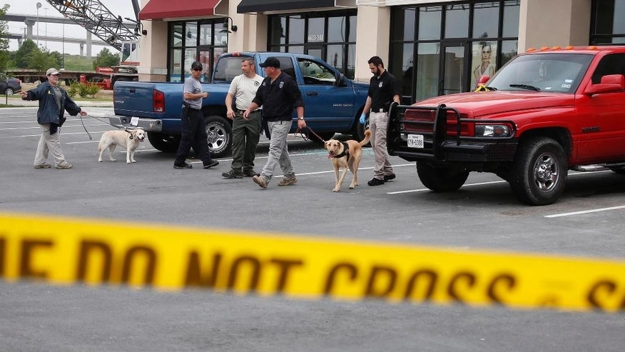 Law enforcement officers use dogs to search parked cars located in part of the Central Texas Marketplace Tuesday, May 19, 2015, in Waco, Texas.  A deadly weekend shootout involving rival motorcycle gangs apparently began with a parking dispute and someone running over a gang member's foot, police said Tuesday. One man was injured when a vehicle struck his foot. That caused a dispute that continued inside the restaurant, where fighting and then shooting began, before spilling back outside, Waco police Sgt. W. Patrick Swanton said.  The shootout left nine people dead injured 18 wounded.   (Rod Aydelotte/Waco Tribune-Herald via AP)