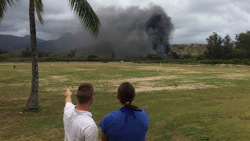 May 17, 2015: A man and woman look toward smoke rising from a Marine Corps Osprey aircraft after making a hard landing on Bellows Air Force Station near Waimanalo, Hawaii. The fatal crash of the Marine Corps' new hybridized airplane-and-helicopter aircraft during a training exercise is renewing safety concerns about the machine. (Zane Dulin via AP)
