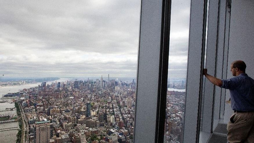 A visitor to One World Observatory looks over Manhattan, Wednesday, May 20, 2015, in New York. The observatory atop the 104-story One World Trade Center opens to the public on May 29. (AP Photo/Mark Lennihan)