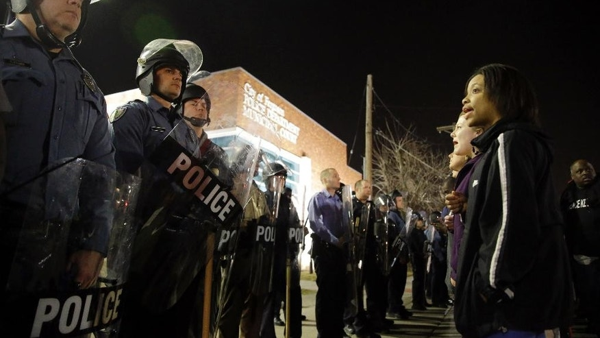 FILE - In this March 11, 2015 file photo, police and protesters square off outside the Ferguson Police Department in Ferguson, Mo.  The prevailing images of protests in Baltimore and Ferguson, Missouri, over police killings of black men were of police in riot gear, handcuffed protesters, tear gas and mass arrests. The main images of a fatal gun battle between armed bikers and police in Waco, Texas, also showed mass arrests _ carried out by nonchalant-looking officers sitting around calm bikers on cell phones. (AP Photo/Jeff Roberson, File)