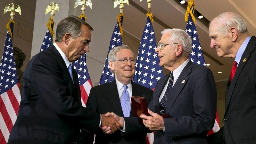 House Speaker John Boehner of Ohio, left, with Senate Majority Leader Mitch McConnell of Ky., second from left, and Rep. Sam Johnson, R-Texas, right, greet retired Air Force Lt. Gen. Charles Cleveland, as they award Cleveland a Congressional Gold Medal on behalf of the American Fighter Aces', Wednesday, May 20, 2015, during a ceremony at Emancipation Hall on Capitol Hill in Washington. (AP Photo/Jacquelyn Martin)