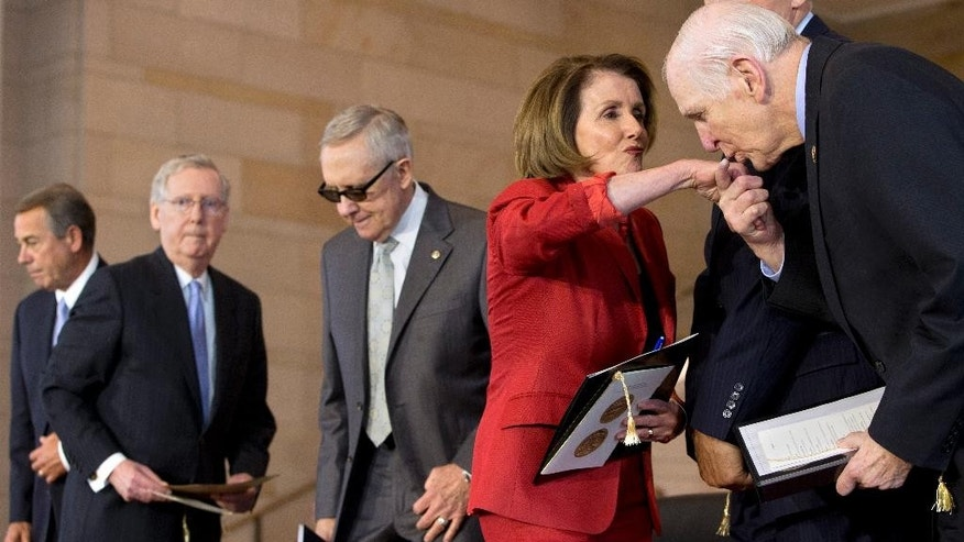 House Minority Leader Nancy Pelosi of Calif., is kissed on the hand by Rep. Sam Johnson, R-Texas, right, as they arrive for a ceremony to present the Congressional Gold Medal to the American Fighter Aces for their service to warfare aviation, Wednesday, May 20, 2015, on Capitol Hill in Washington. From left are, House Speaker John Boehner of Ohio, Senate Majority Leader Mitch McConnell of Ky., and Senate Minority Leader Harry Reid of Nev. (AP Photo/Jacquelyn Martin)
