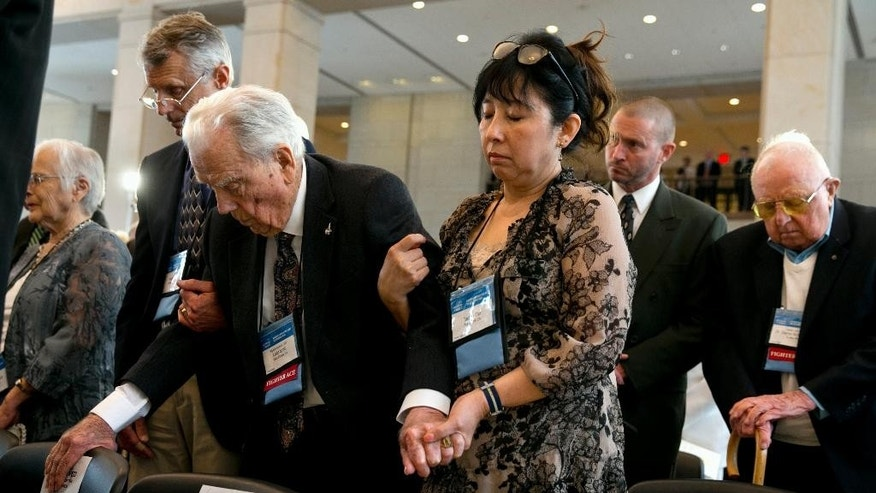 Rand Smith, left, of Mooresville, N.C., helps his father Fighter Ace Air Force Brigadier Gen. Leslie Smith, 96, of Walnut Creek, Calif., to stand with help from Smith's caregiver Taehee Cho, during a prayer at a ceremony awarding the Congressional Gold Medal to the American Fighter Aces, Wednesday, May 20, 2015, on Capitol Hill in Washington. At right is Fighter Ace, retired Army Air Force Captain Clayton Kelly Gross, of Sparks, Nev. (AP Photo/Jacquelyn Martin)