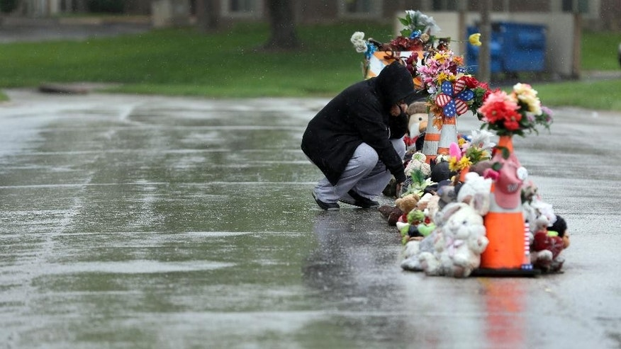 Volunteers remove items left at a makeshift memorial to Michael Brown Wednesday, May 20, 2015, in Ferguson, Mo. The memorial that has marked the place where Brown was fatally shot by a police officer in August has been removed and will be replaced with a permanent plaque, Ferguson's Mayor James Knowles said Wednesday. (AP Photo/Jeff Roberson)