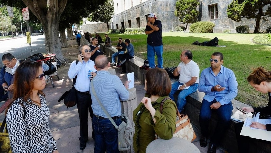 People who were evacuated from a federal building and a nearby building wait in front of the U.S. Courthouse in downtown Los Angeles on Wednesday, May 20, 2015. Police have arrested a woman who they say made a bomb threat, prompting two buildings to be evacuated and streets to be closed. Police Officer Tony Im says the woman was arrested Wednesday about three hours after making the threat in the lobby of a federal building around 11 a.m. (AP Photo/Richard Vogel)