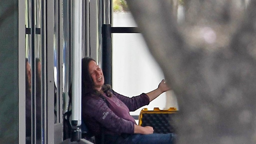A woman sits in front of the downtown Los Angeles Federal Building with a package Wednesday, May 20, 2015. Police Officer Tony Im said the woman was arrested Wednesday about three hours after making a bomb threat. The threat prompted two buildings to be evacuated and streets to be closed in downtown Los Angeles. (AP Photo/Nick Ut)