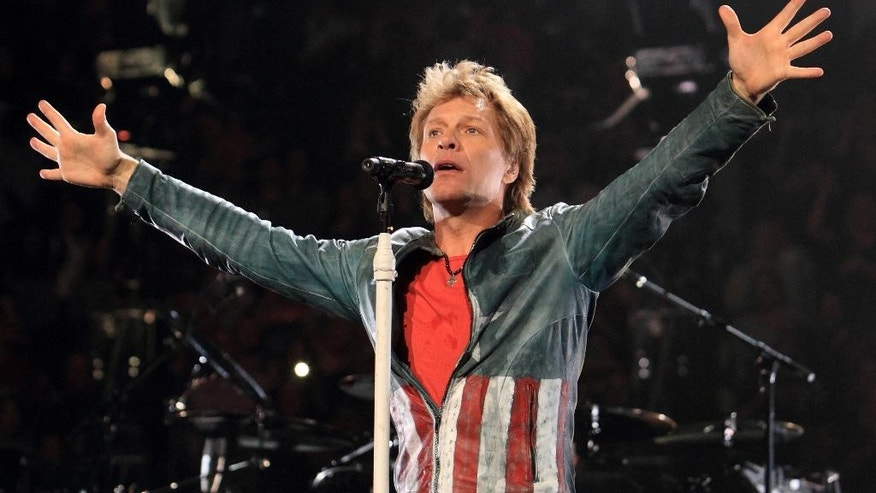 FILE - In this Nov. 5, 2013 file photo, Jon Bon Jovi performs in concert with his band Bon Jovi on their Because We Can Tour 2013, in Philadelphia. The rocker is home in New Jersey to address the graduates of Rutgers University's Camden campus and receive an honorary degree. The commencement ceremony on Thursday, May 21, 2015, is being held at the Susquehanna Bank Center, a concert venue where his band Bon Jovi, has performed in the past.  (Photo by Owen Sweeney/Invision/AP, File)