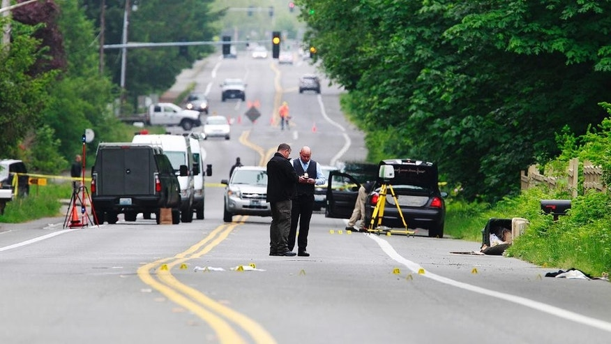 Investigators comb the scene of an officer-involved shooting Thursday, May 21, 2015 in Olympia,Wash. Police in the capital of Washington state say an officer shot two men in their 20s suspected of trying to steal beer from a grocery store. (Steve Bloom/The Olympian via AP)