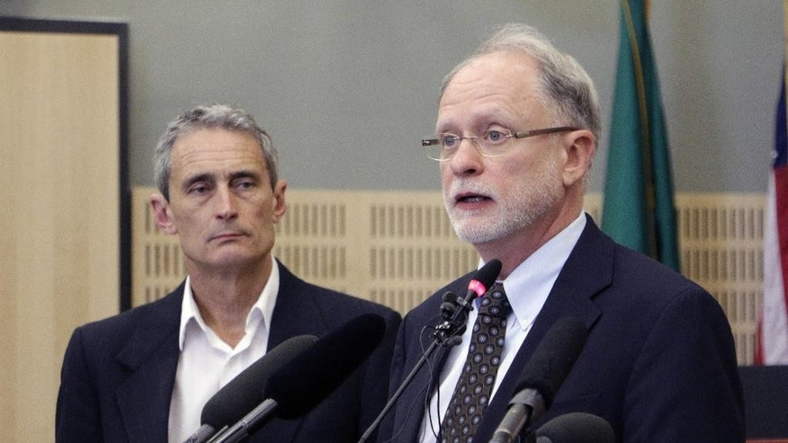 City Mayor Stephen H. Buxbaum, right, speaks to the media about a police-involved shooting as City Manager Steve Hall, left, looks on, Thursday, May 21, 2015, in Olympia, Wash. Police say that two stepbrothers suspected of trying to steal beer from a grocery store were not armed when they were shot by a police officer who later confronted them. (AP Photo/Rachel La Corte)