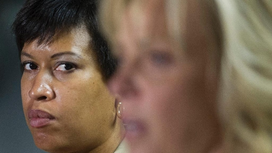 Washington Mayor Muriel Bowser listens at left as Police Chief Cathy Lanier speaks during a news conference in Washington, Thursday, May 21, 2015, to discuss the investigation into the mysterious slayings of a wealthy Washington family and their housekeeper. Lanier said investigators believe a suspect in the slayings is in the Brooklyn area of New York City.  (AP Photo/Cliff Owen)