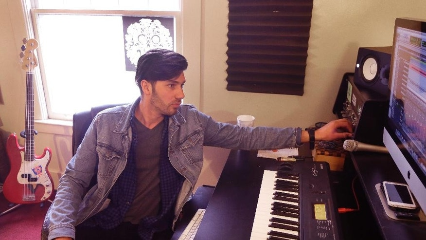 """In this April 23, 2015 photo, music producer Mike Seger works in his studio in a rented two-story house on  Detroit's east side. Seger, 27, pays $750 per month in rent, and said he wouldn't have been able to find anything comparable in the suburbs for that price. """"A young person can move here with $10,000 and start up a small flex space for artists or artists' studios,"""" Seger said. """"It's the uprising of the youth being able to have the opportunities to make a future for themselves."""" (AP Photo/Carlos Osorio)"""