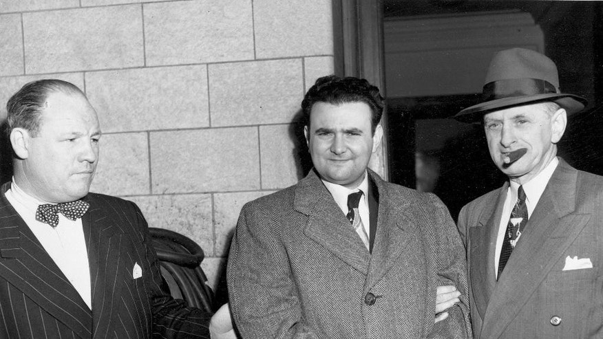 FILE- In this April 6, 1951 file photo, a handcuffed David Greenglass is escorted by U.S. Deputy Marshall Eugene Fitzgerald from Federal Courthouse in New York City after being sentenced to 15 years in prison for conspiracy to spy for the Soviet Union. Greenglass, whose grand jury testimony helped send his sister and brother-in-law, Ethel and Julius Rosenberg, to the electric chair in 1953, has said in interviews that prosecutors pressured him to falsify information about his sister.  (AP Photo)