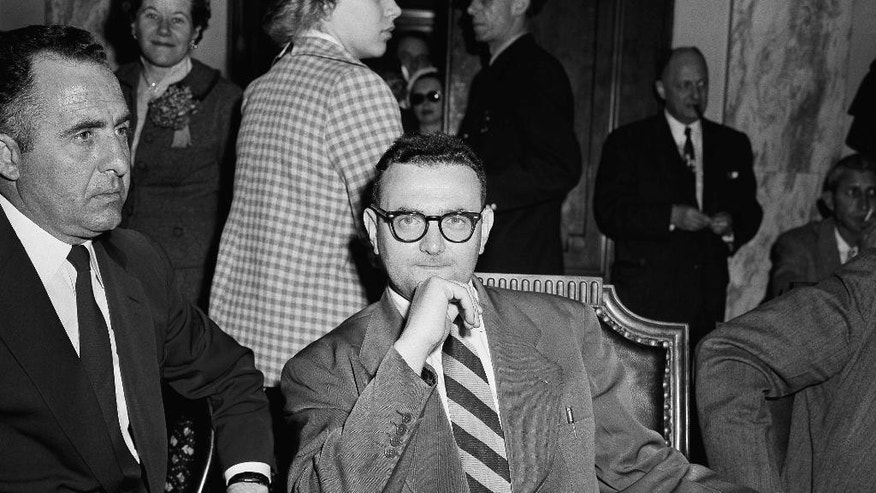 FILE - In this April 26, 1956, file photo, David Greenglass sits beside Deputy U.S. Marshal Joseph Oreto, left, in Washington. A federal judge in New York ordered the release of Greenglass's grand jury testimony from 1950, saying that it can be released because Greenglass died in 2014 at age 92. The ruling may give new fuel to suspicions that Greenglass' sister, Ethel Rosenberg, was unjustly convicted of espionage and put to death in 1953 for conspiring to give nuclear secrets to the Soviet Union.  (AP Photo/Henry Griffin, File)