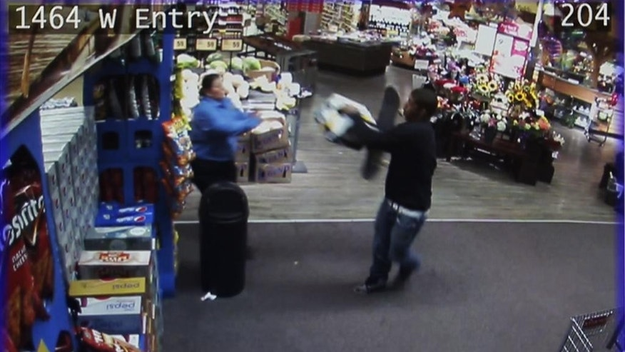 In this image made from Thursday, May 21, 2015 security camera video and released by the Thurston County Sheriff's Office on Friday, a Safeway employee, left, stands in front of a man in the store in Olympia, Wash. An Olympia police officer responded around 1 a.m. Thursday to a 911 call from the store and reported he was being assaulted with a skateboard before shooting and wounding Bryson Chaplin and Andre Thompson near the store. (Thurston County Sheriff's Office via AP)