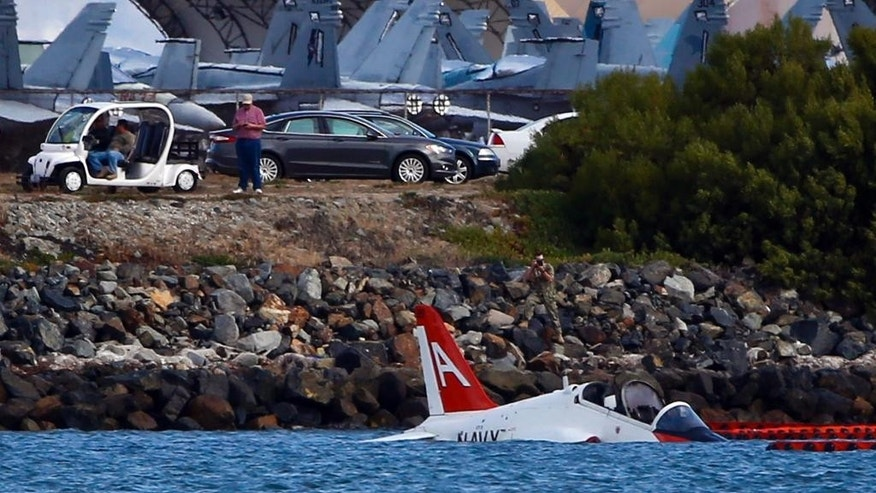 A US Navy aircraft sits in shallow water in San Diego Bay after over shooting a runway at the North Island Naval Station Friday, May 22, 2015 in San Diego. The pilot ejected and was reportedly picked up by a civilian craft. (AP photo/Lenny Ignelzi)