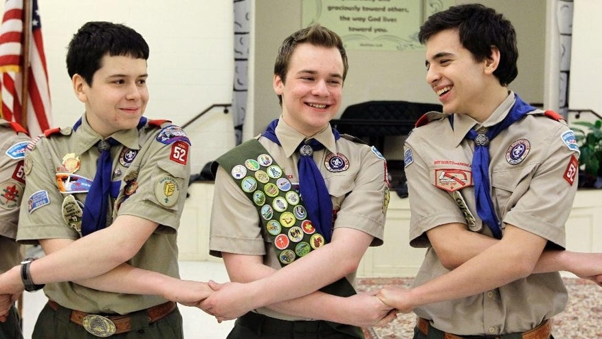 FILE - In this Monday, Feb. 10, 2014 file photo, Pascal Tessier, center, takes part in an activity with fellow scouts Matthew Huerta, left, and Michael Fine, right, after he received his Eagle Scout badge in Chevy Chase, Md. On Thursday, April 2, 2015, the Boy Scouts' New York chapter announced it hired Tessier as the nation's first openly gay Eagle Scout as a summer camp leader in public contrast to the national scouting organization's ban on openly gay adult members. (AP Photo/Luis M. Alvarez)