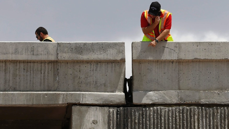 May 22, 2015: Workers inspect damage to a freeway ramp.
