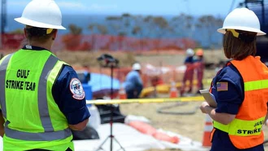 May 22, 2015: This photo from the U.S. Coast Guard shows two members of the Coast Guards Strike Team surveying the site of the pipeline break in the hills above Refugio Beach north of Goleta, Calif.(AP)
