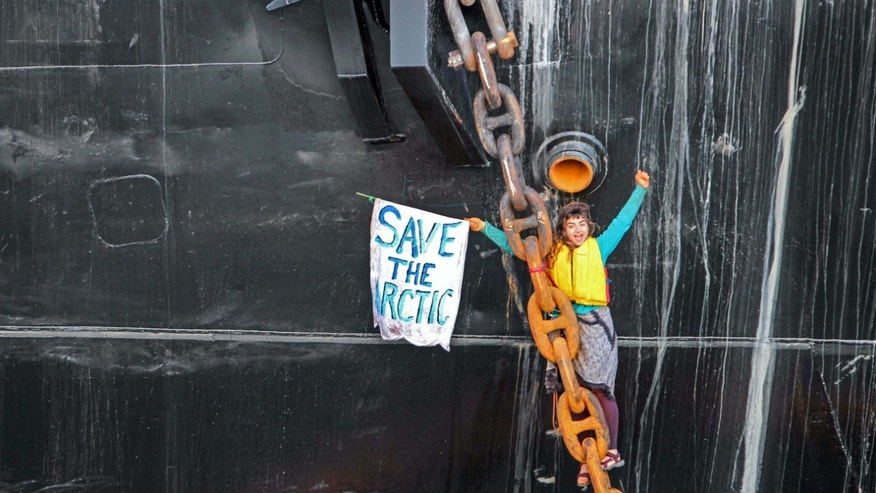 May 22, 2015: A woman identified as Chiara Rose has suspended herself in a climbing harness from the anchor chain of the Royal Dutch Shell support ship Arctic Challenger in the harbor at Bellingham, Wash.