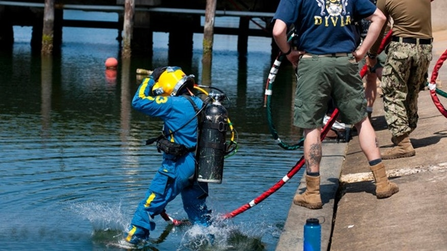 May 14, 2015: This image provided by the U.S. Navy, Navy diver 1st class Jason Geissler, left, assigned to Mobile Diving Salvage Unit (MDSU) 2, performs a front-step water entry during training at Joint Expeditionary Base Little Creek-Fort Story in Virginia Beach, Va.