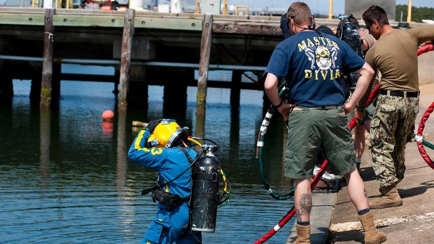 In this Thursday, May 14, 2015 photo provided by the U.S. Navy, Navy diver 1st class Jason Geissler, left, assigned to Mobile Diving Salvage Unit (MDSU) 2, performs a front-step water entry during training at Joint Expeditionary Base Little Creek-Fort Story in Virginia Beach, Va. During this training divers are preparing for an upcoming assignment to salvage of the Civil War ironclad Confederate State Ship (CSS) Georgia in the Savannah Rive in Savannah, Ga. (Petty Officer 2nd class Heather Brown/U.S. Navy via AP)