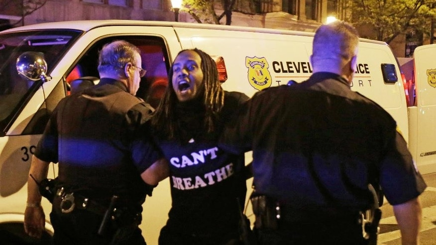 A protester is arrested after the acquittal of Michael Brelo, a patrolman charged in the shooting deaths of two unarmed suspects Saturday, May 23, 2015, in Cleveland. Brelo, who fired down through the windshield of a suspect's car at the end of a 137-shot barrage that left the two unarmed black occupants dead, was acquitted Saturday of criminal charges by a judge who said he could not determine the Cleveland officer alone fired the fatal shots.  (AP Photo/Tony Dejak)