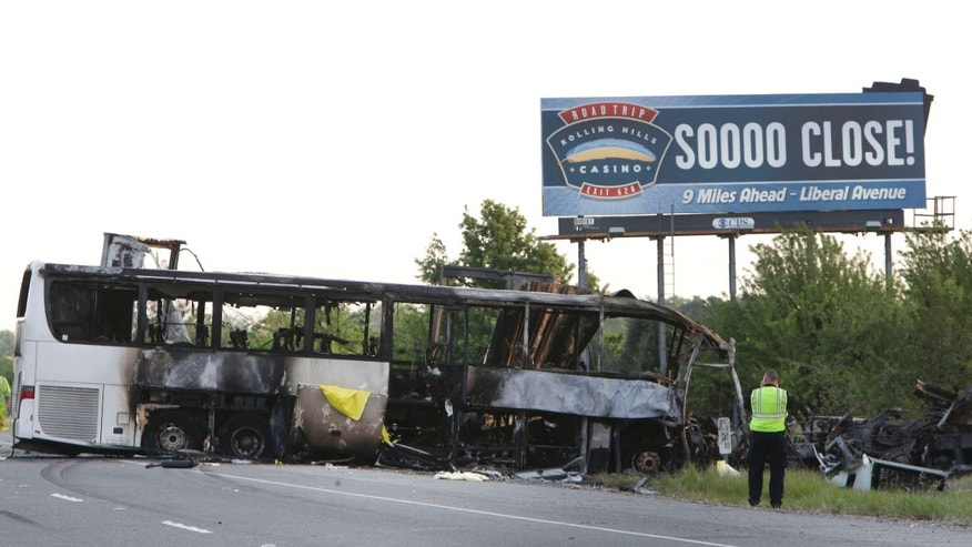 April 11, 2014: A California Highway Patrol Officer photographs the crash scene where a tour bus and a FedEX truck crashed on Interstate 5 in Orland, Calif.