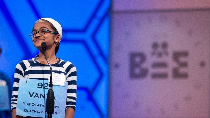 "File-This May 30, 2012, file photo shows Vanya Shivashankar, of Olathe, Kan., smiling as she answers her question during the third round of the National Spelling Bee in Oxon Hill, Md.  Participants and bee officials say the competition is fairer now that kids are tested on what words mean. But it's also taken some of the drama away from the semifinal rounds. Thirteen-year-old Vanya Shivashankar says she misses the simplicity of the old format, which she called ""spelling till you drop."" Now, there are two semifinal rounds, and test scores determine who makes it to the finals. Vanya was eliminated at that stage last year.  (AP Photo/Evan Vucci, File)"